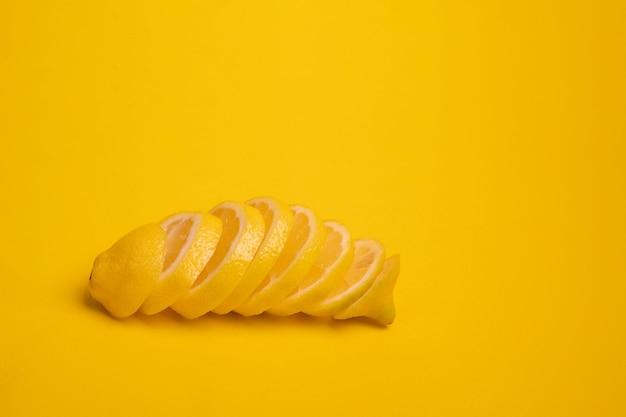 Een in plakjes gesneden citroen ligt op een gele achtergrond. banner