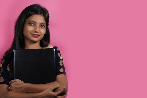 Een indiase vrouw poseert met een laptop