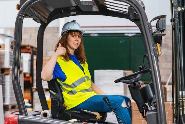 Een industriële vrouwelijke werknemer lachend in een heftruck in een magazijn