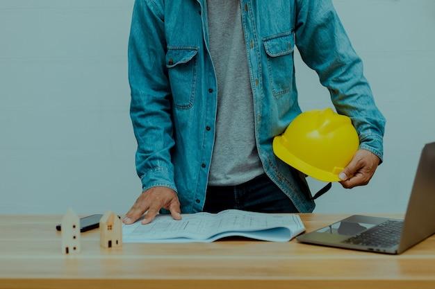 Een ingenieur die een bouwhelm vasthoudt