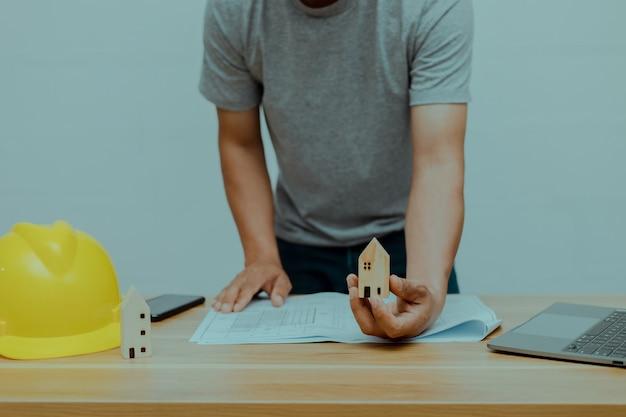 Een ingenieur die een houten huisje vasthoudt