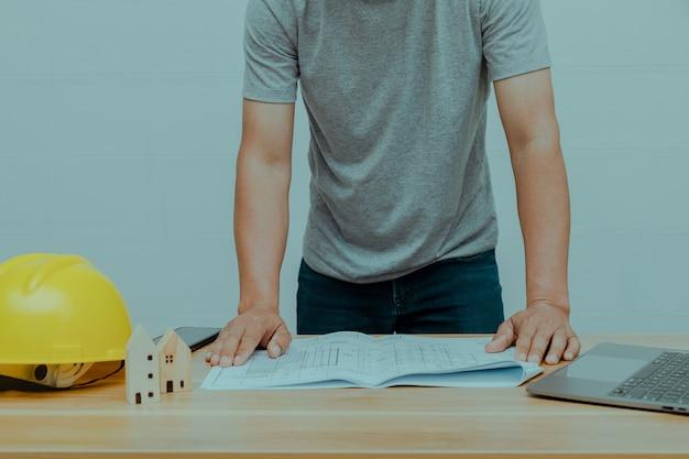 Een ingenieur die een woningbouwplan bekijkt