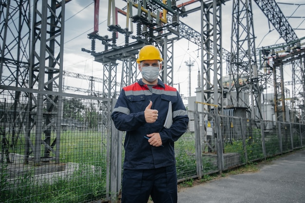 Een ingenieur elektrische onderstations inspecteert moderne hoogspanningsapparatuur in een beschermend masker. energie. industrie.