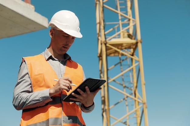 Een ingenieur in een oranje vest en een witte constructiecontrolehelm voert een inspectie uit met een tablet in zijn handen tegen de van een bouwplaats en een torenkraan