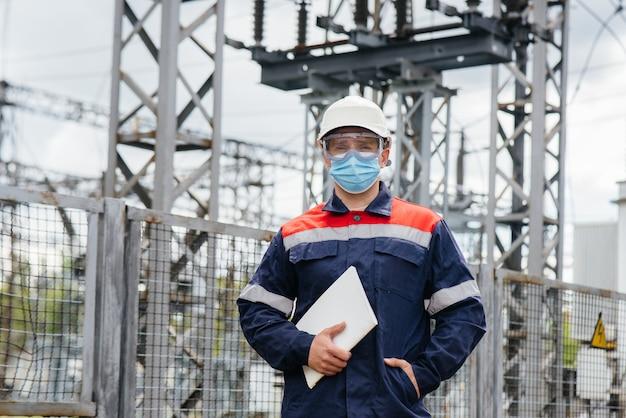 Een ingenieur in het onderstation inspecteert moderne hoogspanningsapparatuur in een masker op het moment van pandemie. energie. industrie.