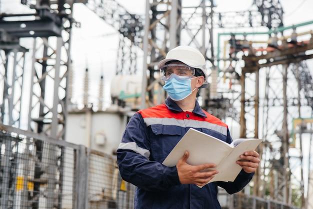 Een ingenieur in het onderstation inspecteert moderne hoogspanningsapparatuur in een masker op het moment van pandemie