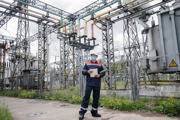 Een ingenieur in het onderstation inspecteert moderne hoogspanningsapparatuur in een masker op het moment van pondemia. energie. industrie.