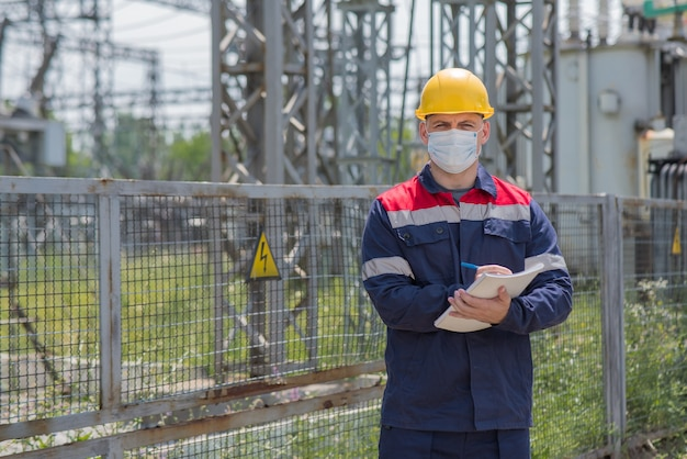 Een ingenieur in het onderstation inspecteert moderne hoogspanningsapparatuur in een masker op het moment van pondemia.