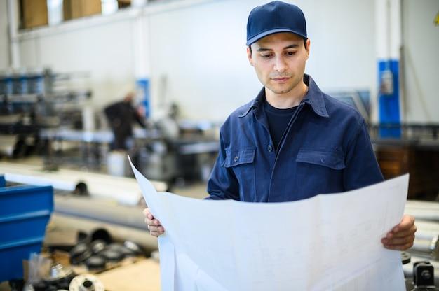Een ingenieur kijkt naar een blauwdruk in een faciliteit