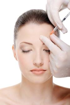 Een injectie in de wenkbrauw op het vrouwelijk gezicht geven - witte ruimte