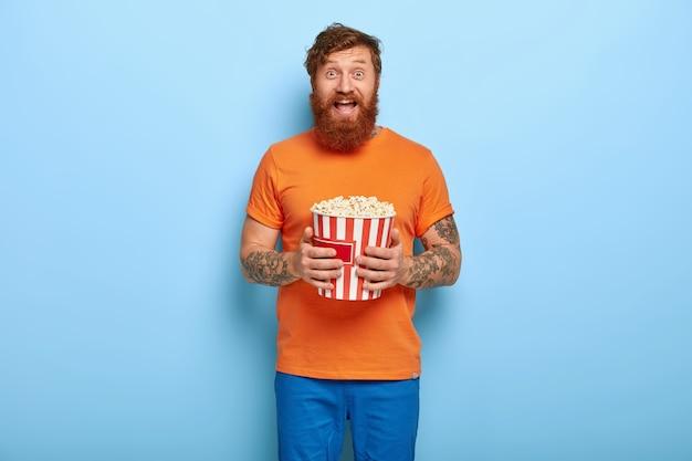Een intens vermaakte roodharige man met een baard eet popcorn