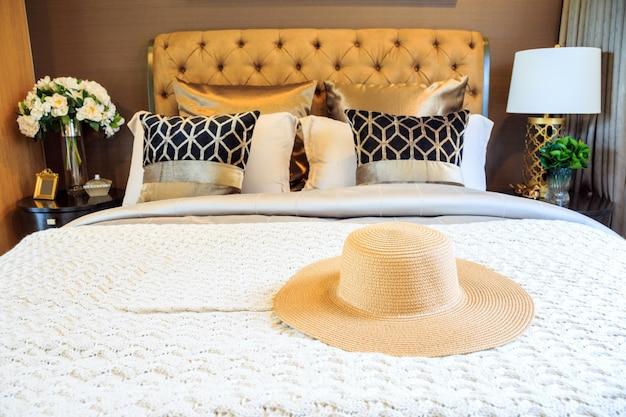 Een interieur slaapkamer ontwerp met lady strooien hoed op luxe bed.