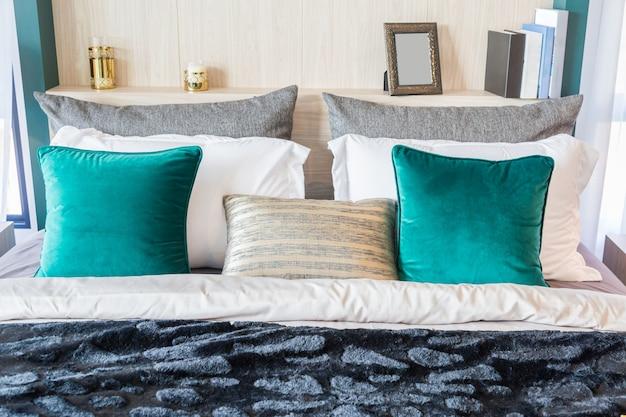 Een interieurfoto van een bed met veel kussens en een zwart fluwelen deken.