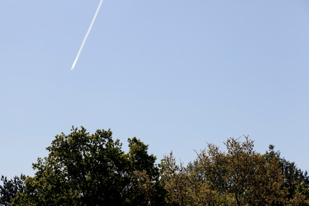Een inversiespoor vanuit een vliegend vliegtuig tegen een blauwe lucht, zonnig helder weer, de techniek liet kunstmatige wolken achter