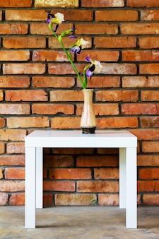 Een irisbloem in een vaas op een witte tafel tegen een bakstenen muurachtergrond brick