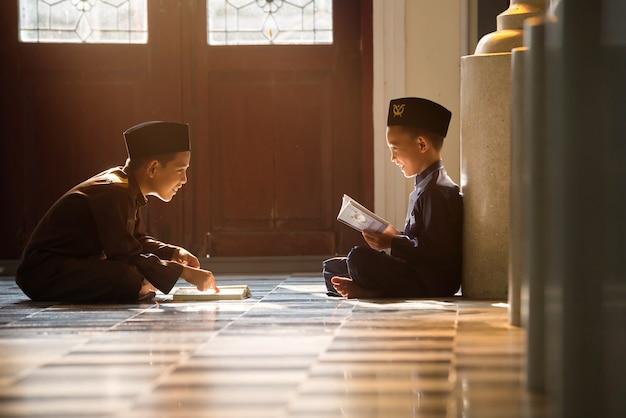 Een islamitisch kind bidt om met zijn zus en broer te studeren in een moskee in songkhla, thailand.