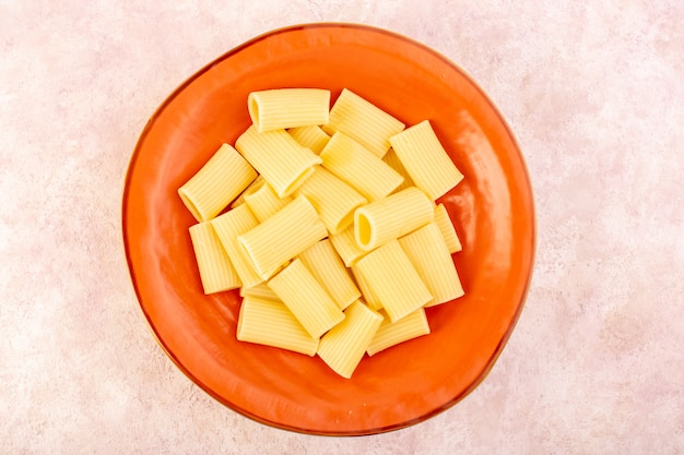 Een italiaanse deegwaren van het hoogste mening, smakelijk gekookt en gezouten binnen ronde oranje plaat op roze bureau