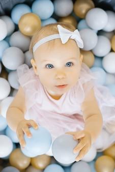Een jaar oud meisje zit in speelgoedballen en ballen houden