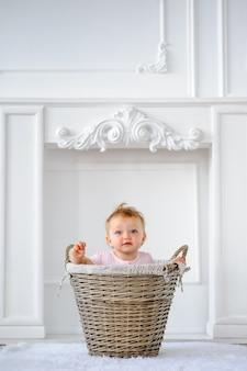 Een jaar oud meisje, zittend in een wasmand.