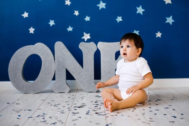Een jaar oude babyjongen in wit t-shirt viert eerste verjaardag in de buurt van zilveren letters one op blauwe muur met sterren.