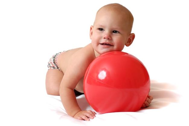 Een jaar oude jongen spelen met grote speelgoed bal op een afgelegen witte achtergrond