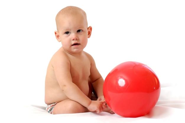 Een jaar oude jongen spelen met grote stuk speelgoed bal op een afgelegen witte achtergrond