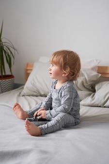 Een jaar oude jongen spelen op het bed met een oude camera, lifestyle foto