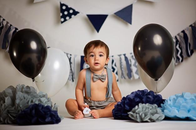 Een jaar oude schattige jongen op een grijze achtergrond