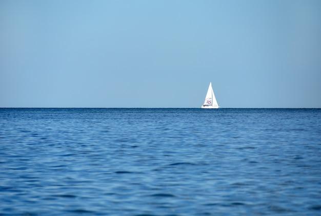 Een jacht met toeristen vaart op de blauwe zee