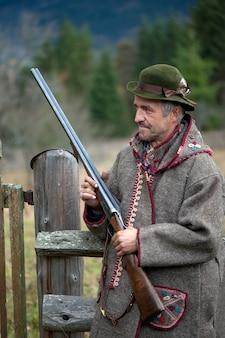 Een jager met een geweer in zijn handen in jachtkleding in het bos op zoek naar een trofee.