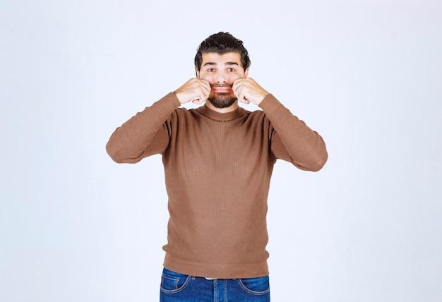 Een jong aantrekkelijk model in bruine sweater die zich over witte muur bevindt.