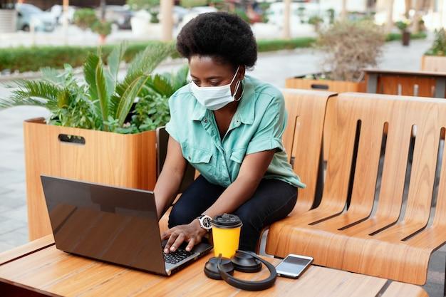 Een jong afrikaans meisje met een medisch gezichtsmasker werkt met een laptop aan een tafel in een café. social distancing en werk, werk online, zakelijk online.