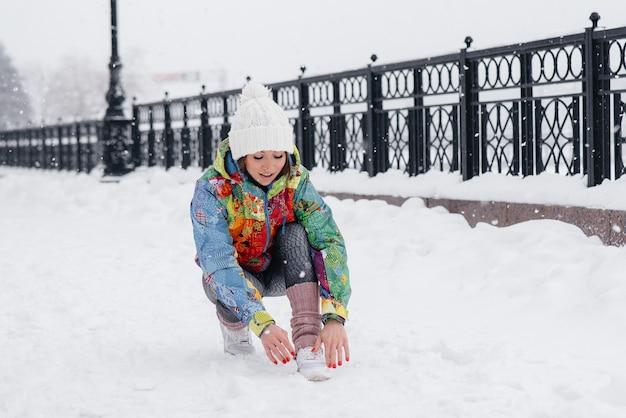 Een jong atletisch meisje knoopt haar schoenen vast op een ijzige en besneeuwde dag. fitness, hardlopen.
