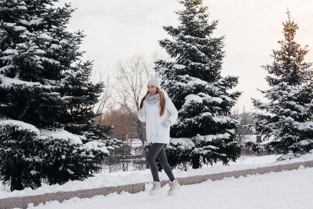 Een jong atletisch meisje loopt in het park op een zonnige winterdag. een gezonde manier van leven.