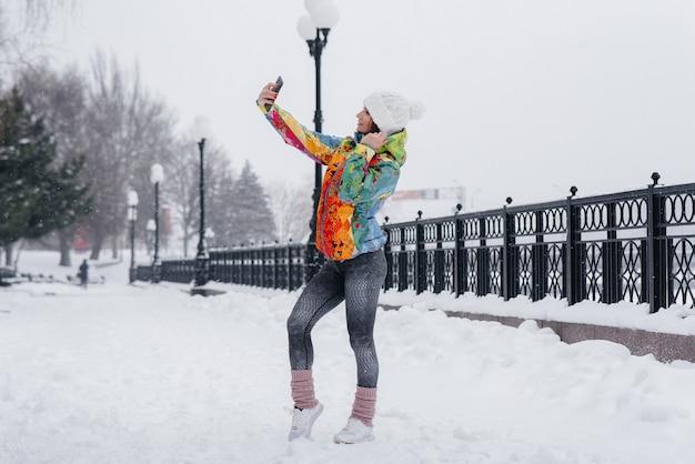Een jong atletisch meisje maakt een selfie op een ijzige en besneeuwde dag. fitness, recreatie