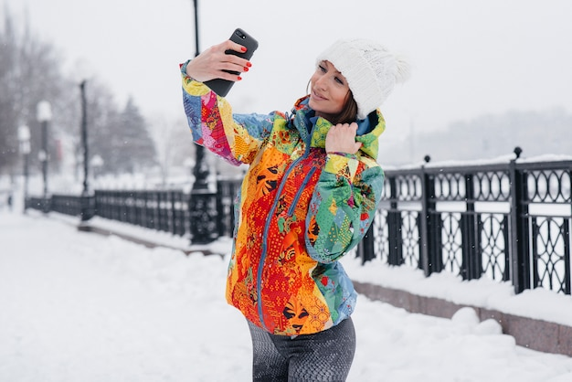 Een jong atletisch meisje maakt een selfie op een ijzige en besneeuwde dag. fitness, recreatie.