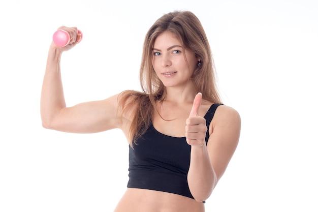 Een jong atletisch meisje toont klasse met de ene hand terwijl de andere haar spieren laat zien