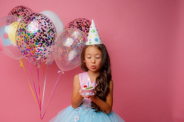 Een jong aziatisch meisje blaast een kaars uit op een roze op een verjaardagsfeestje