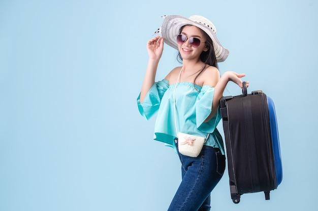 Een jong aziatisch meisje met een helder gezicht, een hoed op en een bril. bagage te houden om te reizen in de zomer in studio blauwe pastel achtergrond. pastelblauwe toonfilters.