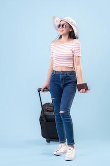 Een jong aziatisch meisje met een helder gezicht, een hoed op en een bril. houden van een paspoort en bagage om in de zomer in studio te reizen blauwe pastelkleurige achtergrond. pastelblauwe toonfilters.