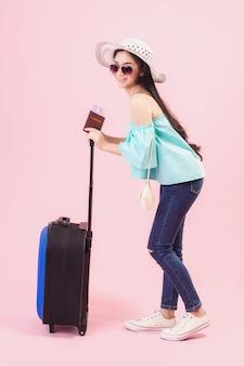 Een jong aziatisch meisje met een helder gezicht, een hoed op en een bril. met een paspoort en bagage om in de zomer te reizen op studio roze pastelachtergrond. pastelroze toonfilters.