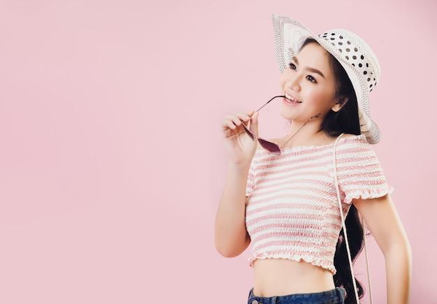 Een jong aziatisch meisje met een helder gezicht, het dragen van een hoed en het dragen van een zonnebril voor een zomervakantie in studio roze achtergrond. pastelroze toonfilters.