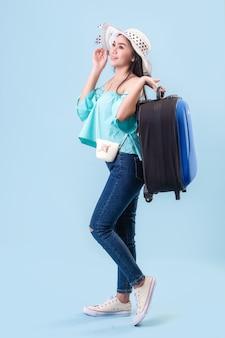 Een jong aziatisch meisje met een helder gezicht, met een hoed op. bagage voor reizen in de zomer in studio houden blauwe pastel achtergrond. pastelblauwe toonfilters.