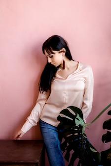 Een jong aziatisch meisje staat tegen een betonnen roze muur naast een enorme bloem en een nachtkastje.