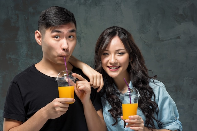 Een jong aziatisch paar met glazen jus d'orange