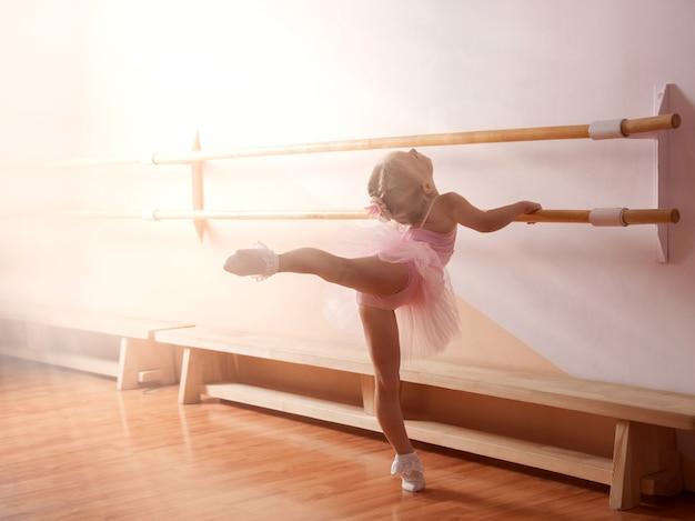 Een jong ballerinameisje in een roze jurk is bezig met een balletstudio
