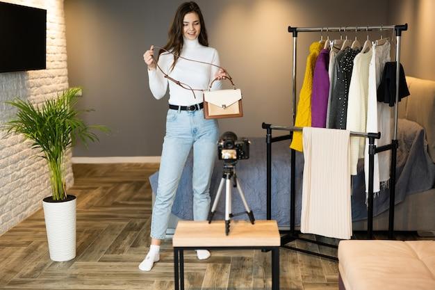 Een jong blogger-meisje met donker haar laat haar kleding en tassen zien aan haar volgers op sociale media om het online te verkopen