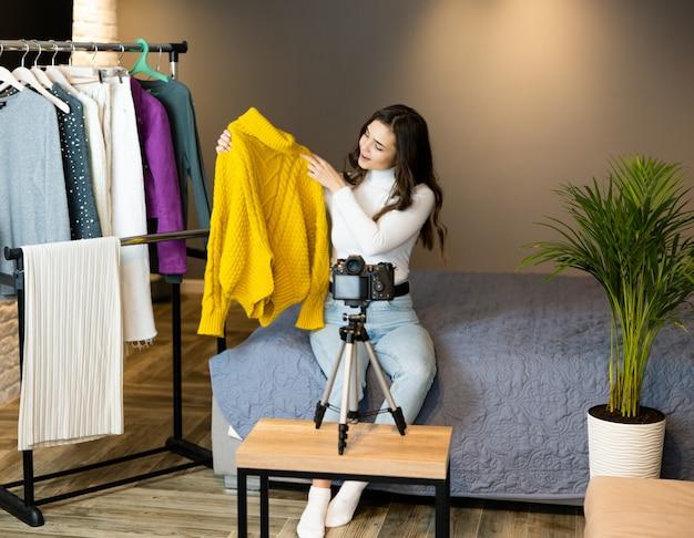 Een jong blogger-meisje met donker haar laat haar kleding zien voor haar volgers op sociale media om het online te verkopen