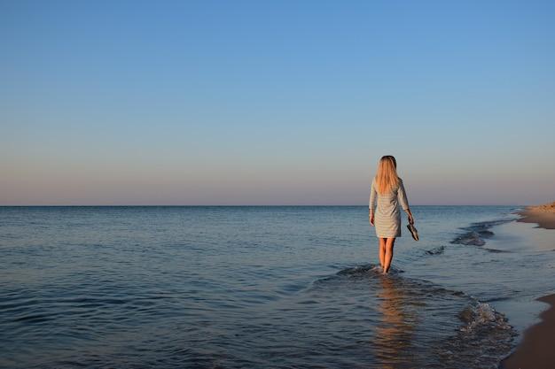 Een jong blond meisje gaat 's ochtends op blote voeten op het strand en draagt schoenen in haar hand. achteraanzicht