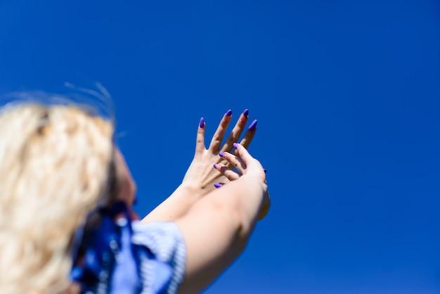 Een jong blond meisje kijkt naar de mooie blauwe lucht en reikt met haar handen naar de hemel. mooie vrouw bewondert de natuur.